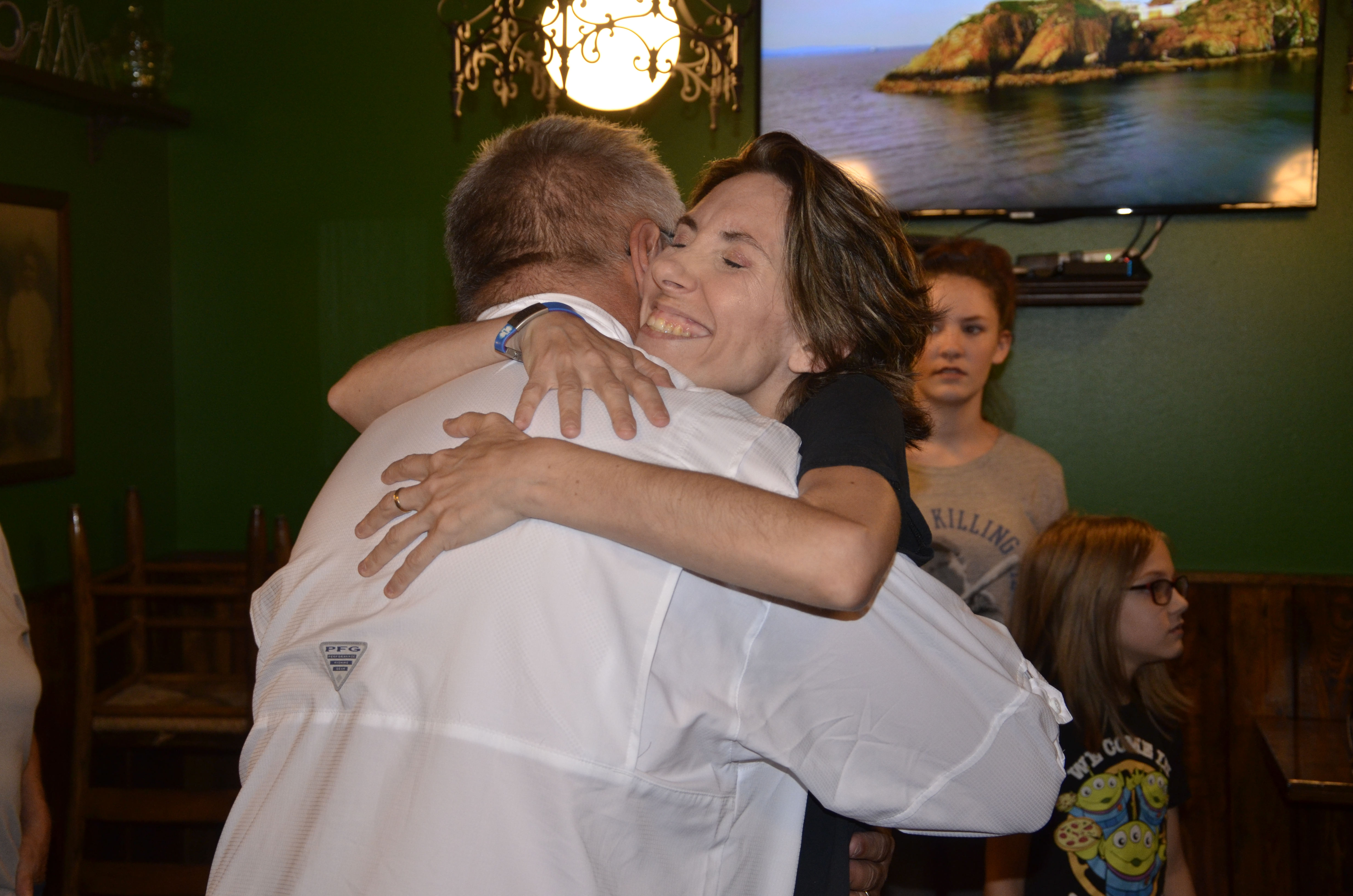 Dawn Wilkerson hugs John Albury on Monday when they met for lunch at Daddy O'Brien's. Albury, a parademic, rushed to Wilkerson's aid during an epileptic seizure at the restaurant in July. (CARL MCKINNEY/Lake City Reporter)