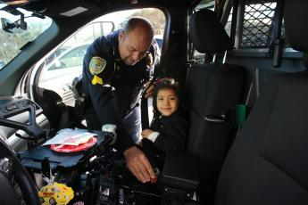 Lake City Police Department officer Robert Milligan belts in Olivia Dillow, 5, as they prepare to head out for the Lake City Police Department after a morning of shopping. (TONY BRITT/Lake City Reporter)