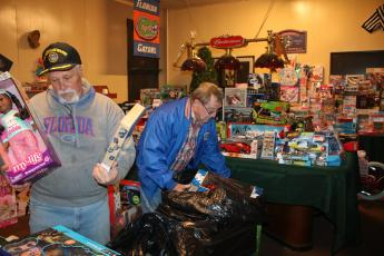 Lake City Elk Club 893 members Michael Lydick (left) and Larry Ward work on arranging toys Thursday afternoon as they prepare for the annual Elks Club Children's Christmas Party, which will take place at about 5 p.m. on Christmas Eve. (TONY BRITT/Lake City Reporter)