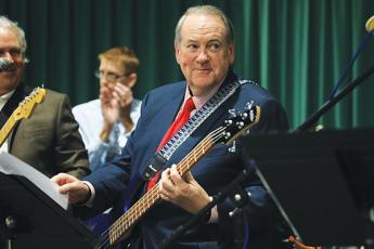 Former Arkansas Governor Mike Huckabee plays bass with local rockers Tuesday night at FGC. (CAMERON VINING/Special to the Reporter)