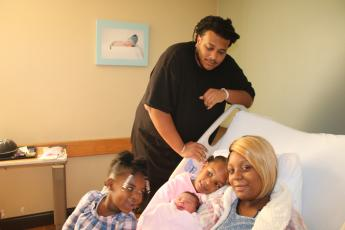 Sariyah Jones (from  left), Aniyah Jones, Alexander Jones and Kadijah Williams pose with Alexis Zakiyah Jones Thursday afternoon. Alexis Zakiyah, who came into the world Wednesday night, was the first baby born in Lake City in 2020. (TONY BRITT/Lake City Reporter)