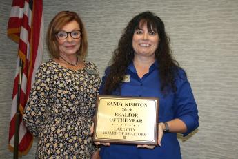 Susan Eagle (left), the 2020 Lake City Board of Realtors President, stands with Sandy Kishton after she presented Kishton with the 2019 Realtor of the Year Award during Monday's Lake City Board of Realtors 2020 Installation Luncheon at the Lake City Holiday Inn. (TONY BRITT/Lake City Reporter)