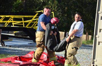 Firefighters lug a search-and-rescue dummy. Friday's drills marked the end of a week-long gauntlet of training exercises, the first time CCFR has hosted personnel from agencies outside the county. (CARL MCKINNEY/Lake City Reporter)