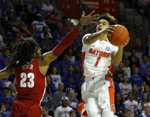 Florida guard Trey Mann goes for a shot around Alabama's John Petty Jr. (23) during Saturday's games at the O'Connell Center. [TRIBUNE NEWS SERVICE)