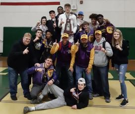 Columbia's wrestling team celebrates is pictured with the trophy after winning the District 2-2A IBT Tournament on Saturday. (COURTESY)