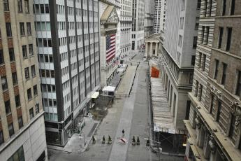 A lone pedestrian wearing a protective mask walks past the New York Stock Exchange as coronavirus concerns empty a typically bustling downtown area in New York on Saturday. (AP FILE PHOTO)