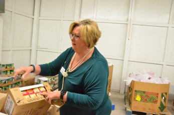 Catholic Charities Regional Director Suzanne Edwards inspects a carton of raisins delivered to the organization's Florida Gateway Food Bank. Demand for food assistance is surging while the economy is in a holding pattern. (CARL MCKINNEY/Lake City Reporter)