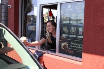 Ellianos manager Lorrain Gleason hands a custom frozen coffee creation through the drive-up window at the business location on U.S. 90 West Tuesday morning in Lake City. Ellianos serves a variety of gourmet Italian coffee and operates a double-drive-through-only business. The company, which is a Lake City-based franchise, has seen business increase during the coronavirus pandemic. (TODD WILSON/Lake City Reporter)