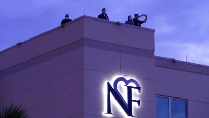 LCMC officials watch the event unfold from the hospital's roof Sunday night. The Orchard Community Church, which organized the event, estimated that a couple hundred automobiles participated. (TRAVIS LEE/Special to the Reporter)
