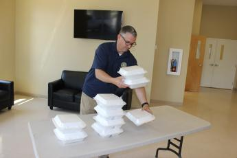 Rotary Club of Lake City Treasurer Mike Tatem stacks boxed-lunch meals at noon Thursday inside the welcome center at Parkview Baptist Church. Rotarians drove through the covered drop-off area of the church, picked up a lunch, then returned home or to their offices before tuning in to the club's first-ever virtual meeting via the on-line platform Zoom. The club normally meets at noon on Thursdays. (TODD WILSON/Lake City Reporter)