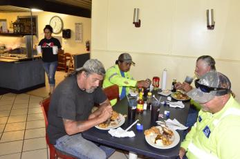 Workers with a local construction company enjoy their first dine-in meal in weeks late Monday morning at the Landing, a family buffet off U.S. 90. Pictured on the front left is Greg Walker, who is joined by Nicholas Flick at right, Aureliano San Juan in the back left and Danny Boone in the back right. (CARL MCKINNEY/Lake City Reporter)
