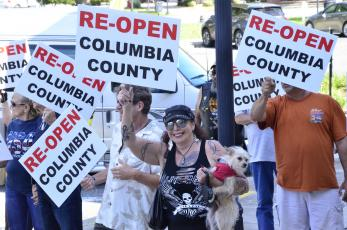 Anti-lockdown protesters march near the Columbia County Courthouse on Tuesday morning. The demonstrators called for all businesses to be allowed to reopen, even as the state has begun relaxing measures in place to curb the spread of covid-19. (CARL MCKINNEY/Lake City Reporter)