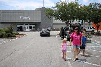 Jordyn Fletcher, 4, walks in the Lake City Walmart Super Center parking lot with Rebecca Fletcher and Jayden Fletcher, 9, Wednesday afternoon while the family was shopping at Walmart without masks. On Wednesday Walmart and Sam's Club announced that effective July 20, customers will be required to wear face coverings when shopping at its stores. (TONY BRITT/Lake City Reporter)