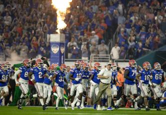 Florida Gators head coach Dan Mullen leads his team out onto the field prior to a game last season. (ALLEN EYESTONE/The Palm Beach Post)
