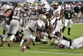 Miami running back Cam'Ron Harris (23) scores a touchdown against Florida State on Saturday, in Miami Gardens. (MICHAEL LAUGHLIN/South Florida Sun-Sentinel via AP)