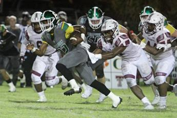 Suwannee running back Malachi Graham tries to pull away from a Madison County defender Friday night at Langford Stadium. (PAUL BUCHANAN/Special to the Reporter)