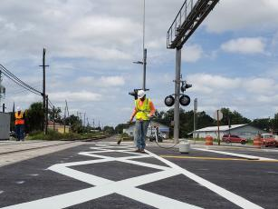 Crews finish work on the dynamic envelopes — giant connecting white X's — at the rail crossing on U.S. Highway 129 (Ohio Avenue) in downtown Live Oak. The crossing reopened Monday night after being closed for two weeks for the improvements, which are part of the Florida Department of Transportation's Operation STRIDE. (COURTESY FDOT)