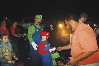 Robert Stalvey and Hagan Stalvey, 7, came dressed as Luigi and Mario at last year's Trunk or Treat. Here Hagan accepts candy from Steven Flores. (FILE)