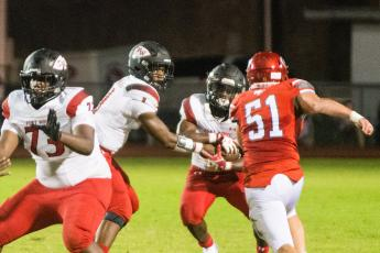 Fort White quarterback Tyler Jefferson hands the ball off to running back Tavion Taylor on Friday night. (CHRISTINA FEAGIN/Special to the Reporter)