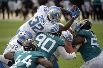 Detroit Lions running back D'Andre Swift (32) leaps over Jacksonville Jaguars linebacker Myles Jack (44) and defensive tackle Taven Bryan (90) for a touchdown on Oct. 18 in Jacksonville. (PHELAN M. EBENHACK/Associated Press))