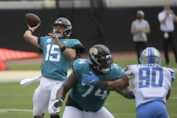 Jacksonville Jaguars quarterback Gardner Minshew II (15) throws a pass as offensive tackle Cam Robinson (74) blocks Detroit Lions defensive end Trey Flowers (90) on Oct. 18 in Jacksonville. (PHELAN M. EBENHACK/Associated Press)