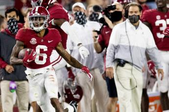 Alabama wide receiver DeVonta Smith (6) heads for a long gain as coach Nick Saban watches during a game against Kentucky on Nov. 21 in Tuscaloosa, Ala. (MICKEY WELSH/The Montgomery Advertiser via AP)