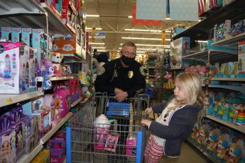 Ryleigh Harden gets a ride on a shopping cart from Lake City Police Department Lt. Andy Miles while Christmas shopping during the Shop with a Cop program Wednesday morning at Walmart. Thirty local children were able to go Christmas shopping with LCPD officers during the event. (TONY BRITT/Lake City Reporter)