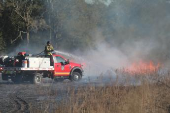 An unidentified firefighter with Columbia County Fire Rescue stands on the back of a brush truck while spraying water on a brush fire Tuesday afternoon. (TONY BRITT/Lake City Reporter)