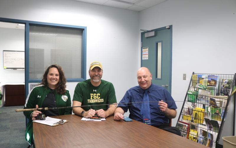 Rebecca Golden (from left), FGC athletic coordinator, sits with Rob Chapman, FGC coordinator of enrollment and marketing and webmaster, and Lawrence Barrett, FGC president, as the three hold a fishing rod and reel during the school's announcement on Friday that it will launch a competitive bass fishing team. The FGC Bassmasters plan to compete during the 2020-21 school year. (TONY BRITT/Lake City Reporter)