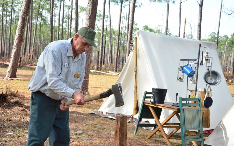 Mark Akers chops firewood at camp. Akers, an artillery coordinator for the Battle of Olustee re-enactment, has been camping at the battlegrounds for several days while he helps to organize one of North Florida's biggest events. (CARL MCKINNEY/Lake City Reporter)