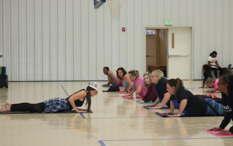Yoga instructor Lisa Lizotte leads school district employees through stretches Tuesday afternoon in the Parkview Baptist Church gymnasium. Twenty-five people attended the first yoga class, offered as part of a school district wellness initiative. (TONY BRITT/Lake City Reporter)