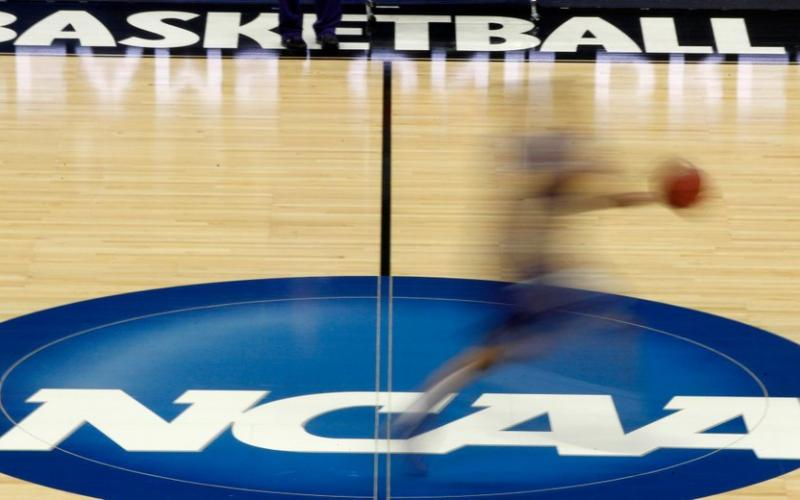 A player runs across the NCAA logo during practice at the NCAA tournament on In this March 14, 2012, in Pittsburgh. (AP FILE PHOTO)
