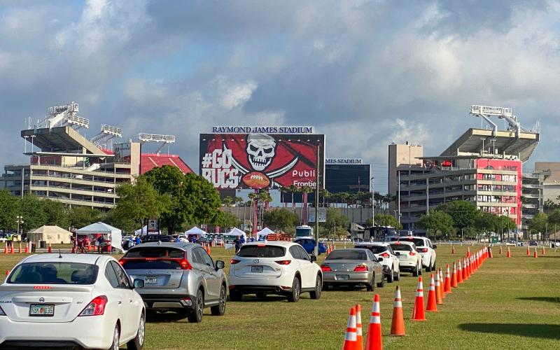Cars are lined up in the parking lot outside of Raymond James Stadium for coronavirus testing on March 25, in Tampa. (LUIS SANTANA/Tampa Bay Times/TNS)