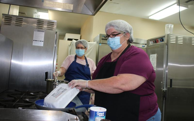 Felecity Houghton (foreground) opens a pack of hamburger while Cindy Brannon stirs a pot of vegetables. (TONY BRITT/Lake City Reporter)