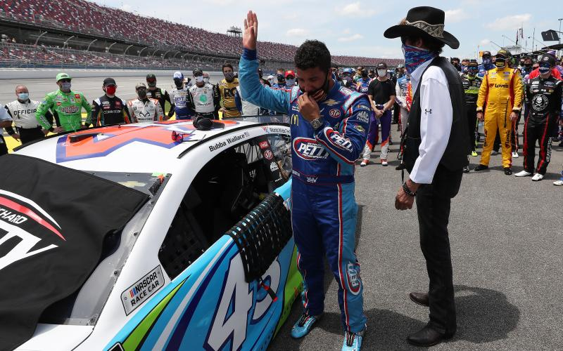 Bubba Wallace, driver of the #43 Victory Junction Chevrolet, and NASCAR Hall of Famer and team owner Richard Petty look on after NASCAR drivers pushed Wallace to the front of the grid as a sign of solidarity with the driver prior to the NASCAR Cup Series GEICO 500 at Talladega Superspeedway on Monday in Talladega, Ala. (CHRIS GRAYTHEN/Getty Images/TNS)