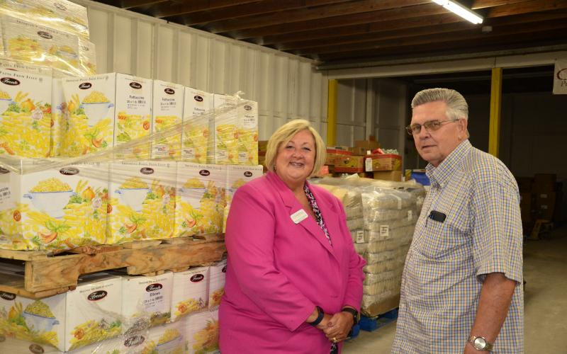 Suzanne Edwards and David Boozer pose together at the Catholic Charities building. The organization's food bank program recently received a $30,000 donation from Nutrien to assist in the covid-19 relief effort. (CARL MCKINNEY/Lake City Reporter)