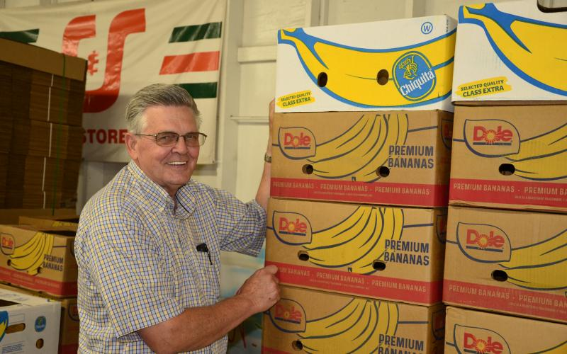 David Boozer, general manager of the Florida Gateway Food Bank, poses in front of the boxes that a shipment of bananas came in. (CARL MCKINNEY/Lake City Reporter)