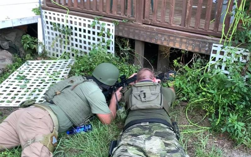 Suwannee County Sheriff's Office SWAT team members look beneath the house where Anthony Riley was hiding Monday. (Courtesy Suwannee County Sheriff's Office)
