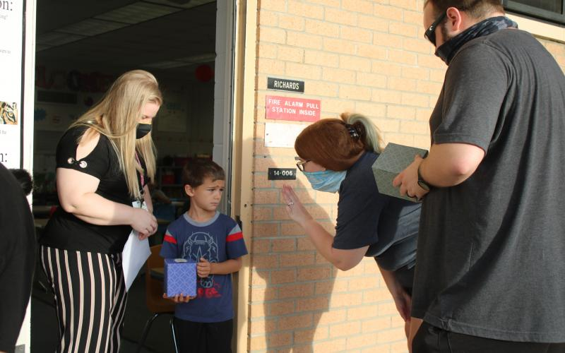 Jessica Richards (from left), a Summers Elementary School kindergarten teacher, looks on as Jayden Wilson watches his parents Ashley DeFreitas and Ryan DeFreitas wave good-bye to him on the first day of school. (TONY BRITT/Lake City Reporter)