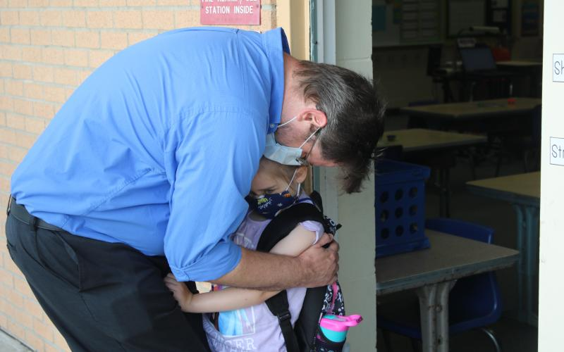 Michael Brock hugs his daughter Artie Brock as he drops her off at a Summers Elementary School kindergarten classroom Monday morning. The Columbia School District started the 2020-21 school year Monday. (TONY BRITT/Lake City Reporter)