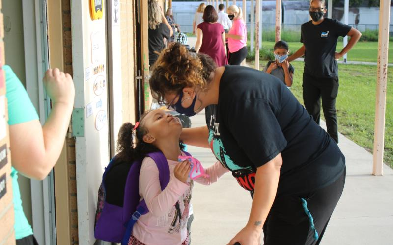 Deziraye Bristol (left) gets a kiss from her mother April Arce before she goes into her Summers Elementary School kindergarten classroom on Monday morning. Due to safety protocols implemented by the school district, parents were only allowed to walk pre-kindergartners and kindergartners to class for the first day of school. (TONY BRITT/Lake City Reporter)