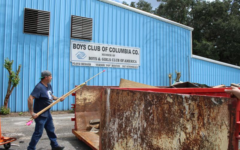 Scott Boisvert throws debris into a dumpster Thursday afternoon while cleaning out the old Boys Club of Columbia County facility. (TONY BRITT/Lake City Reporter)