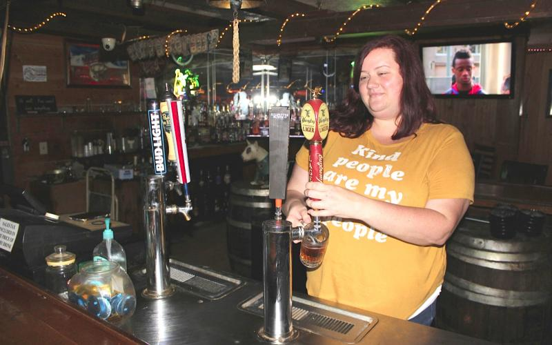 Longbranch Saloon Managing Partner Anita Irwin pulls a Yuengling draught for a customer soon after opening Monday afternoon. Florida bars were allowed to open at 50 percent capacity Monday after covid-19 shutdown restrictions were lifted by the governor. The Longbranch, one of Lake City's oldest bars, re-opened as a non-smoking venue. (TODD WILSON/Lake City Reporter)