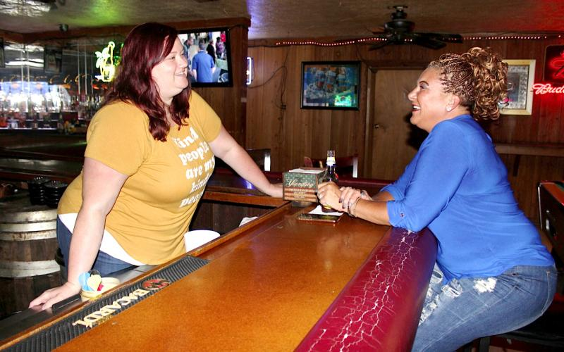 Longbranch Saloon Managing Partner Anita Irwin (left) talks with customer Cheryl Knight Monday afternoon at the bar. The Longbranch opened Monday after being closed 162 days during the government-mandated covid-19 shutdown. (TODD WILSON/Lake City Reporter)