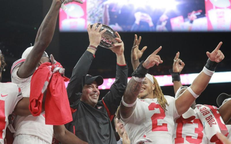 Ohio State coach Ryan Day holds up the trophy after their 34-21 come from behind win over Wisconsin at the Big Ten Championship Game at Lucas Oil Field on Dec. 7 2019, in Indianapolis. (DAVID PETKIEWICZ/cleveland.com/TNS)