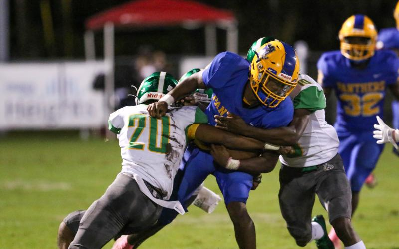 Suwannee's Travis McKinney (left) and Jay Smith stop Palatka quarterback O'marrion Wilson on a run Friday night. (PALATKA DAILY NEWS)