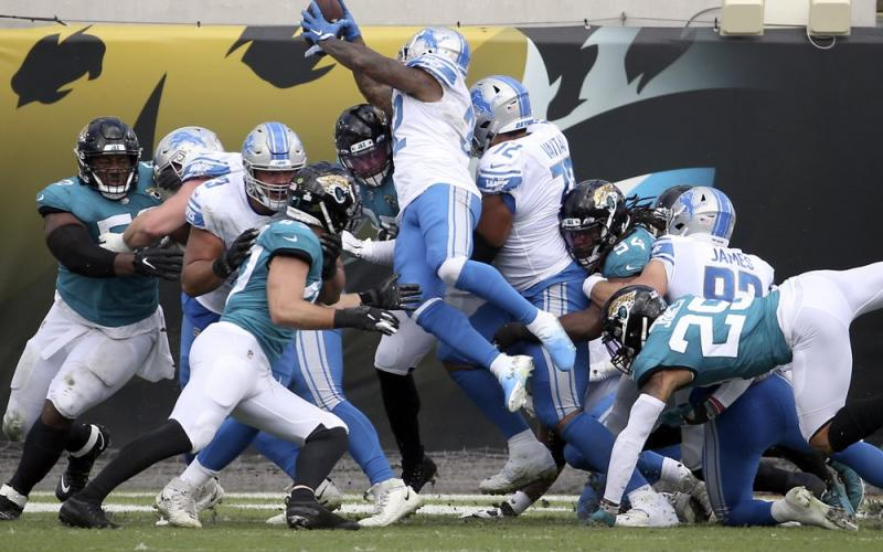 Detroit Lions running back D'Andre Swift (32) leaps over Jacksonville Jaguars linebacker Myles Jack (44) and defensive tackle Taven Bryan (90) for a touchdown on Sunday in Jacksonville. (PHELAN M. EBENHACK/Associated Press)