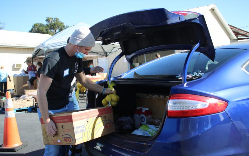Jared Fraze, a Covenant Community School student, puts bags of food into a client's car during Thursday's Catholic Charities Thanksgiving basket giveaway. (TONY BRITT/Lake City Reporter)