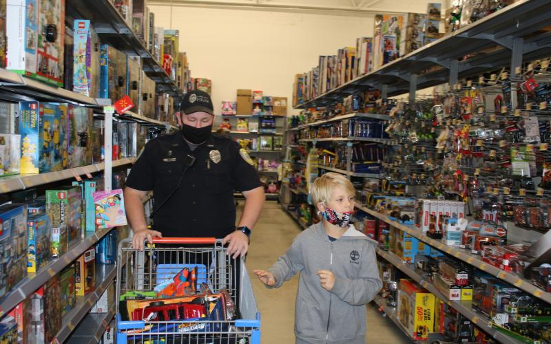 Lake City Police Department Officer Michael Craig looks at a shopping cart full of items as Wyatt Russo looks at more toys for potential Christmas gifts. (TONY BRITT/Lake City Reporter)