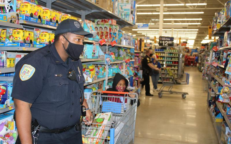 Lake City Police Officer Tyrone Sheppard casts an intent look at prices as he helps a child look for Christmas gifts Wednesday. (TONY BRITT/Lake City Reporter)